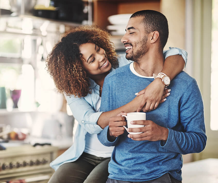 couple drinking coffee embracing and smiling
